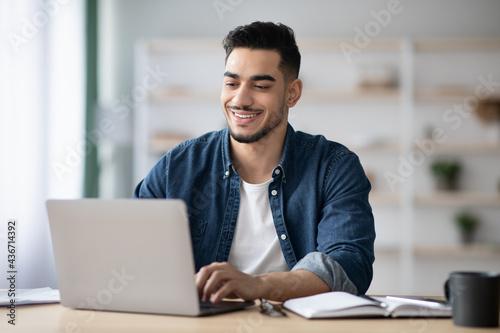 Fotografija Cheerful arab guy working on laptop, typing on keyboard