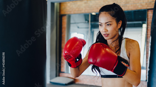 Fotografía Young Asia lady kickboxing exercise workout punching bag tough female fighter practice boxing in gym fitness class