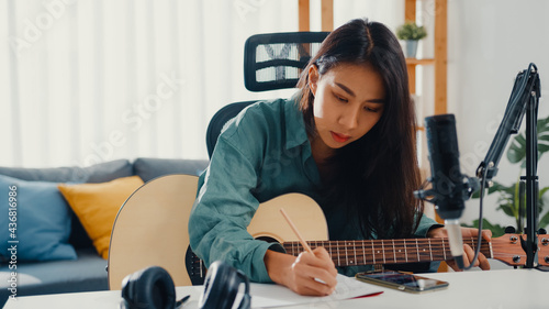 Obraz na plátně Happy asia woman songwriter play acoustic guitar listen song from smartphone think and write notes lyrics song in paper sit in living room at home studio