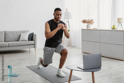 Fotografie, Tablou African Man Training At Laptop Doing Forward Lunge At Home