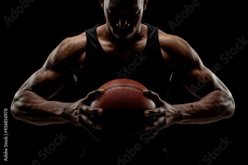 Basketball player holding a ball against black background Fototapet