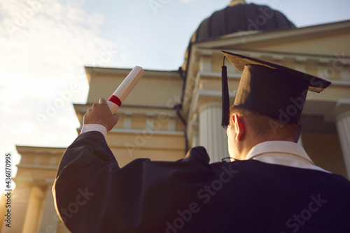 Wallpaper Mural Student wearing gown and academic hat raising diploma degree certificate closeup rear view from bottom