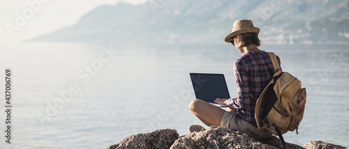 Young woman using laptop computer, working by a sea. Freelance work, vacations, business, people, technologies, distance studying, e-learning, lifestyle, meeting online, web call concept. Banner