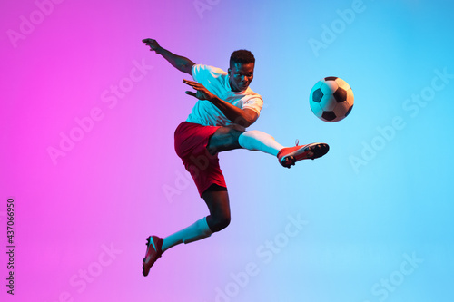 Tablou Canvas One African man, professional soccer football player training isolated on gradient blue pink background in neon light