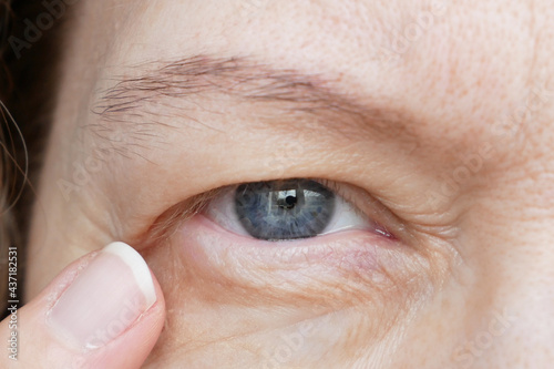 middle-aged woman does corrective eye makeup to correct the drooping eyelid Fototapeta