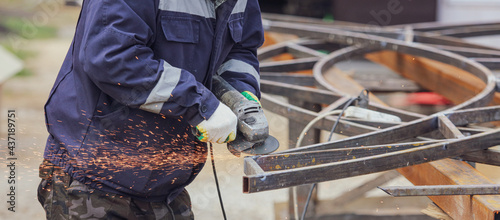 Fotografia, Obraz Sparks from metal cutting at a construction site. Technologies