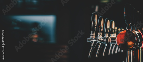 Photographie many beer taps in bar or pub