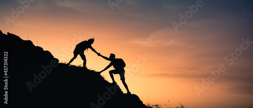 Obraz na plátně Hikers climbing a mountain giving a helping hand up the cliff