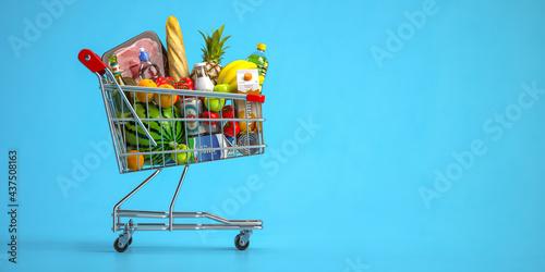 Fotografie, Tablou Shopping cart full of food on blue background