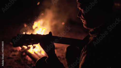 Fotografering Man is playing guitar by the campfire in nature