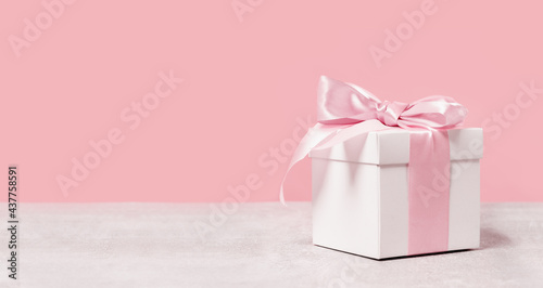 White gift box with shining pink ribbon bow on pink background. Gift or holiday concept. Mothers Day, birthday wedding or St Valentines day banner with copy space