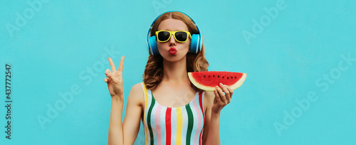 Fotografering Summer fashion portrait of young woman in headphones listening to music with jui