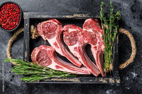 Fotografie, Obraz Raw lamb meat chops steaks in a wooden tray