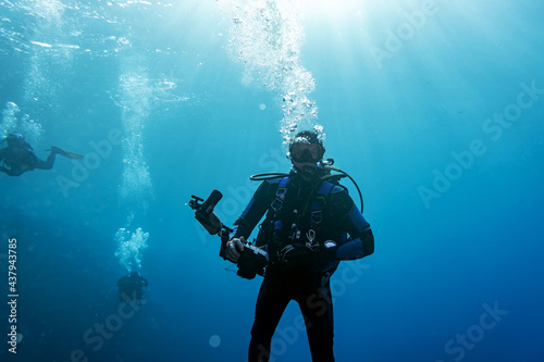 Obraz na plátně diver with equipment for underwater shooting underwater on a blue background