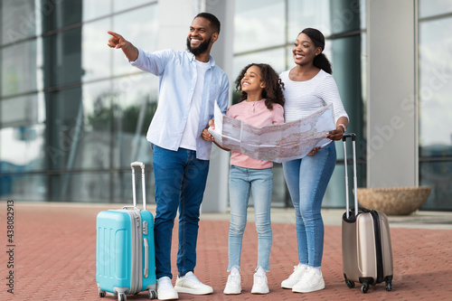 Fotografie, Obraz Happy black family traveling with kid, holding map
