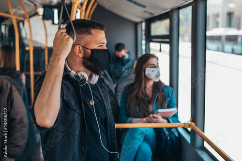 Tablou Canvas Young man wearing protective mask while riding a bus