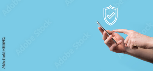 Canvas-taulu Male hand holding protect shield with a check mark icon on blue background