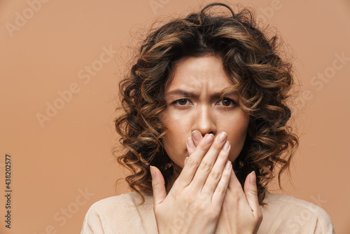 Fototapeta Young curly hispanic woman frowning and covering her mouth