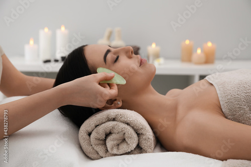 Stampa su Tela Young woman receiving facial massage with gua sha tool in beauty salon