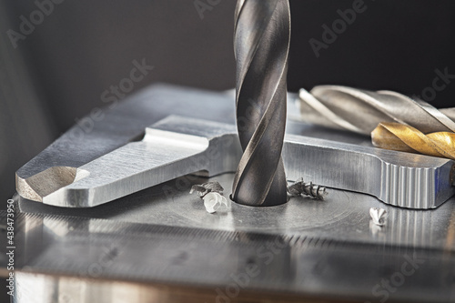 Canvas-taulu drill bit make holes in steel billet on industrial drilling machine with ruler and caliper