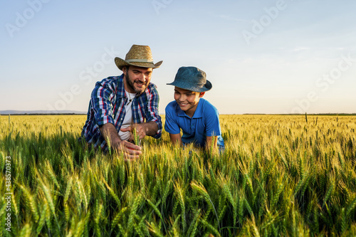 Father and son are standing in their growing wheat field Fototapete