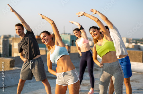 Fényképezés Group of happy friends working out together outdoors