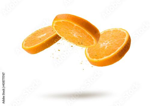 Orange fruit slices flying and dripping on white background Fototapet
