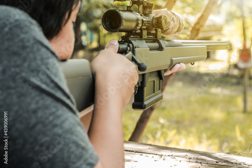 Photo Camouflage sniper shooting rifle by looking through a scope hunting