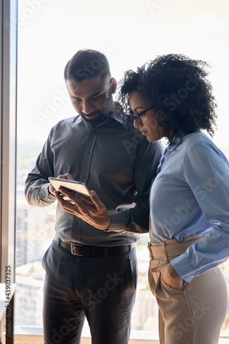 Obraz na płótnie Indian male executive manager mentor consulting on financial operations female African American colleague intern using tablet device standing in modern office near panoramic window