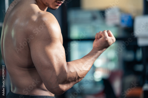 Strong Bodybuilder show muscles and biceps after exercise in fitness Fotobehang