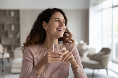 Cuadros en Lienzo Smiling young Hispanic woman hold glass enjoy clean mineral water look in distance dreaming visualizing