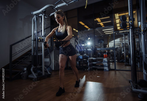 Fit woman workout at dark fitness center and using Cable crossover machine for exercise at her chest and arms. Healthy lifestyle Fitness and sport concept