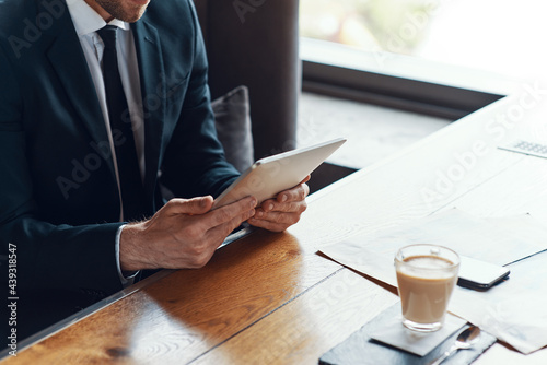 Close up of young businessman in full suit using digital tablet while sitting in Fototapet