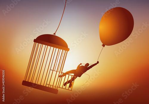 Concept de l'évasion et du rêve de liberté, avec un homme qui quitte une cage à oiseau en s'envolant avec un ballon de baudruche Fototapet
