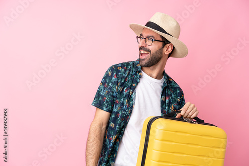 Photo Young caucasian man over isolated background in vacation with travel suitcase an