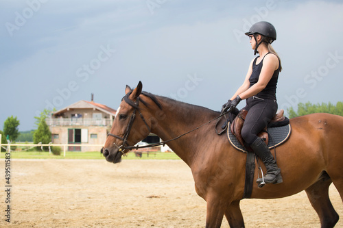 Fotografija A girl in black on a horse at a riding school