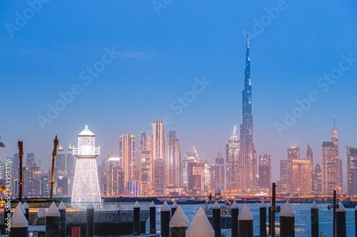 Illuminated decorative lighthouse at the background of famous Burj Khalifa skyscraper tower in the Dubai Creek Marina Harbor Fotobehang