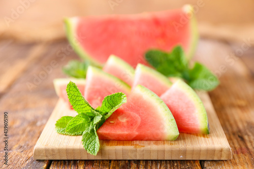 Canvas Print juicy watermelon and slices on wooden board