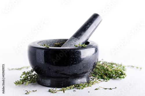 Fotografia Bunch of fresh herbs in gray stone mortar with pestle