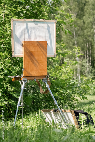 Foto Artist's easel stands among the summer plein air greenery