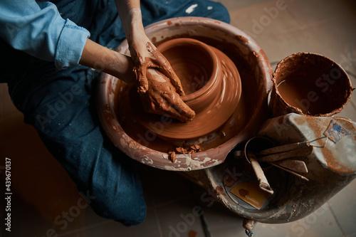 Beautiful elegant ceramicist hands shaping ceramic bowl on pottery wheel in work Fototapeta