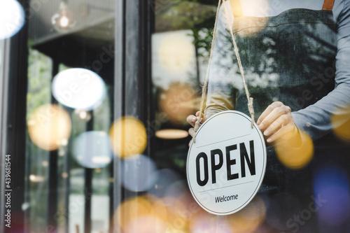 Fotografía hand of asain staff woman wearing apron turning open sign board on glass door in