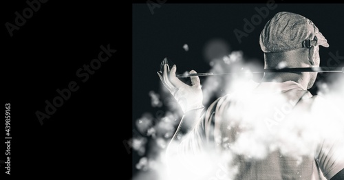 Rear view of senior male golf player holding gold club against smoke effect on black background