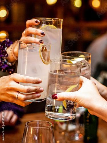 Fotografie, Obraz Vertical shot of girlfriends having cheers on their cocktail drinks