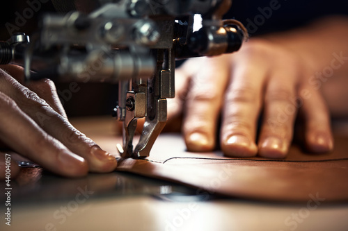 Fotografia, Obraz A sewing machine foot with the hands of a master close-up, a tailor makes a seam