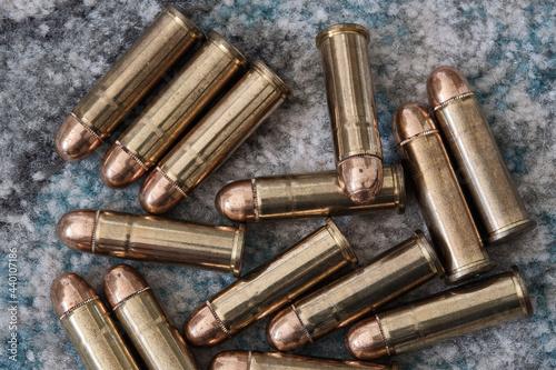 Fotografiet Brass handgun ammunition against a wooden backdrop