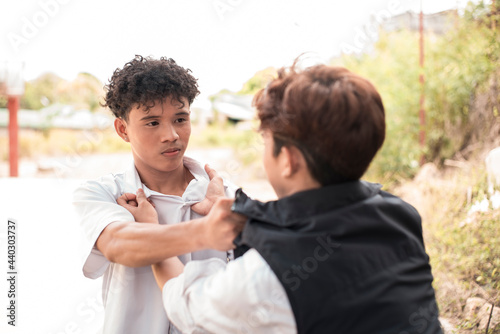 Fotografija A young asian man has a fistfight or dispute with a friend outdoors