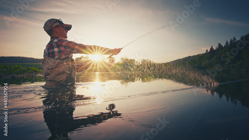 Canvas-taulu Fly fisherman stands in the water and casts the fly with fishing rod using Roll