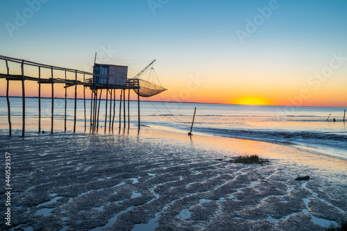 Carta da parati Sunset over the Gironde estuary during low tide at with traditional fishing hut