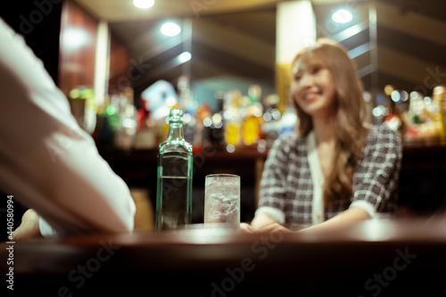 Fotografia カウンターバーでお酒を提供する若い女性
